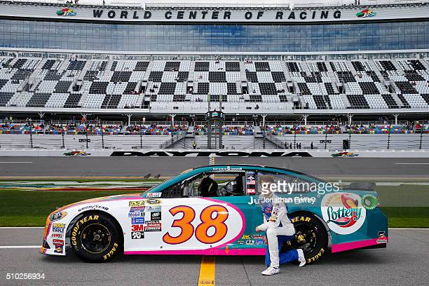 Landon Cassill driver of the Florida Lottery Ford poses with his car after qualifying for the NASCAR Sprint Cup Series Daytona 500 at Daytona...