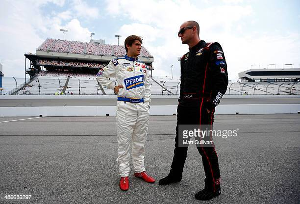 Landon Cassill driver of the GK Services Chevrolet talks to Josh Wise driver of the Curtis Key Plumbing Chevrolet on the grid during qualifying for...