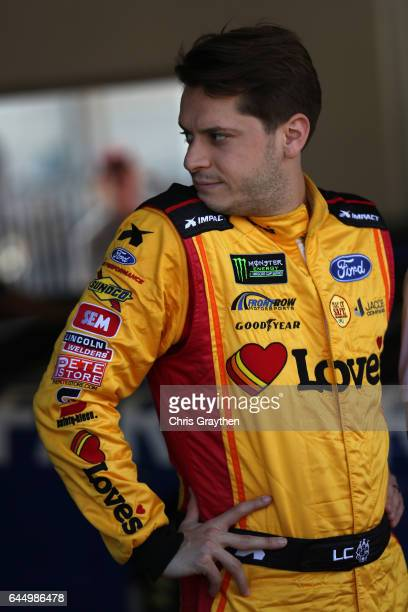 Landon Cassill driver of the Love's Ford stands in the garage area during practice for the 59th Annual DAYTONA 500 at Daytona International Speedway...