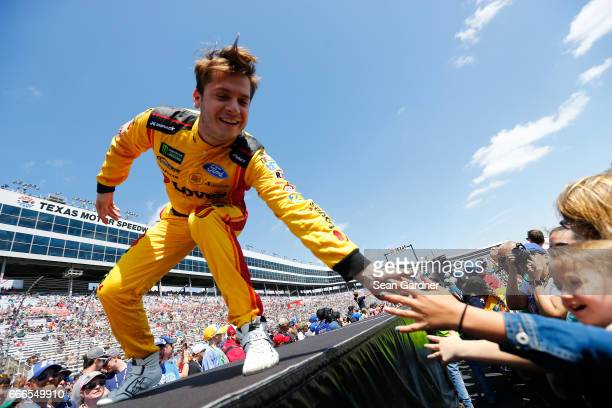 Landon Cassill driver of the Love's Travel Stops Ford greets fans during driver introductions prior to the Monster Energy NASCAR Cup Series O'Reilly...