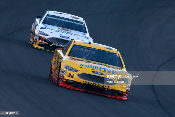 Landon Cassill driver of the Love's Travel Stops Ford leads David Ragan driver of the Brandeis/Komatsu Ford during the Monster Energy NASCAR Cup...