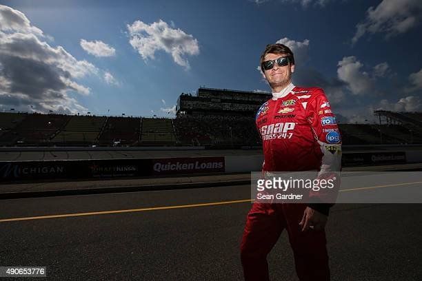 Landon Cassill driver of the Snap Fitness Chevrolet stands on the grid during practice for the NASCAR Sprint Cup Series Pure Michigan 400 at Michigan...