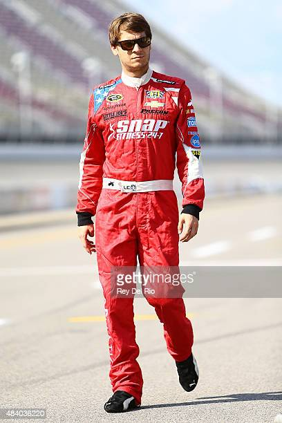 Landon Cassill driver of the Snap Fitness Chevrolet walks on pit road during qualifying for the NASCAR Sprint Cup Series Pure Michigan 400 at...