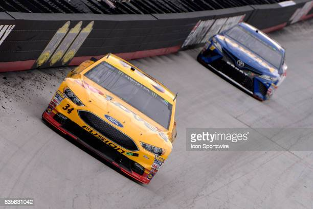 Landon Cassill Front Row Motorsports Ford Fusion leads Daniel Suarez Joe Gibbs Racing Toyota Camry down the back stretch during practice for the Bass...