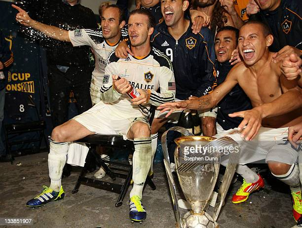 Landon Donovan and David Beckham of the Los Angeles Galaxy celebrate in the locker room after defeating the Houston Dynamo 10 in the 2011 MLS Cup at...