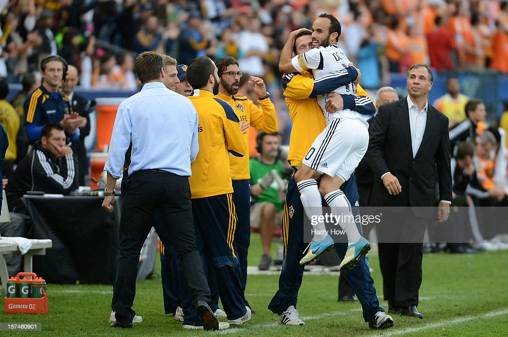 Landon Donovan #10 of Los Angeles Galaxy celebrates with a member of the coaching staff in front of head coach Bruce Arena while taking on the Houston Dynamo in the 2012 MLS Cup at The Home Depot Center on December 1, 2012 in Carson, California.