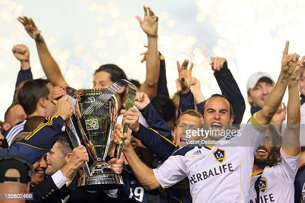 Landon Donovan of the Los Angeles Galaxy and his teammates celebrate with the Philip F Anschutz Trophy on the podium after defeating the Houston...