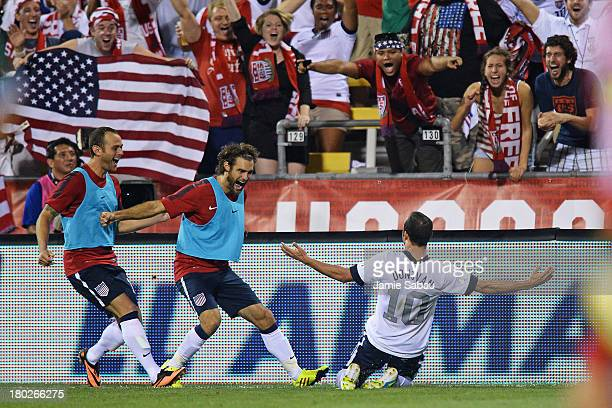 Landon Donovan of the United States Men's National Team celebrates his second half goal against Mexico with teammates Brad Davis of the United States...