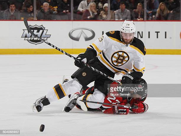 Landon Ferraro of the Boston Bruins lands on top of Jordin Tootoo of the New Jersey Devils during the third period at the Prudential Center on...