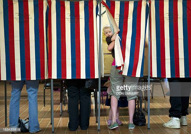 Landon Peterson peeks out of the voting booth while his mother Meghan votes March 20 2012 at Christian union Church in Metamora Illinois White House...