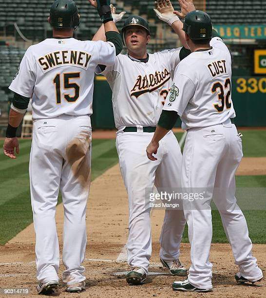 Landon Powell of the Oakland Athletics is greeted at home plate by teammates Ryan Sweeney and Jack Cust after hitting a grand slam home run against...