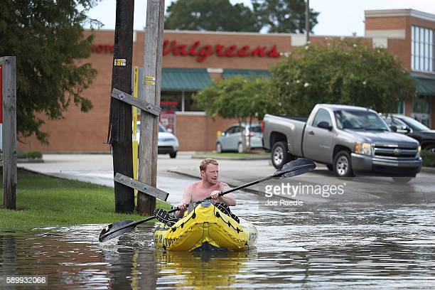 Landon Stanly navigates through a flooded street to his home on August 15 2016 in Baton Rouge Louisiana Recordbreaking rains pelted Louisiana over...