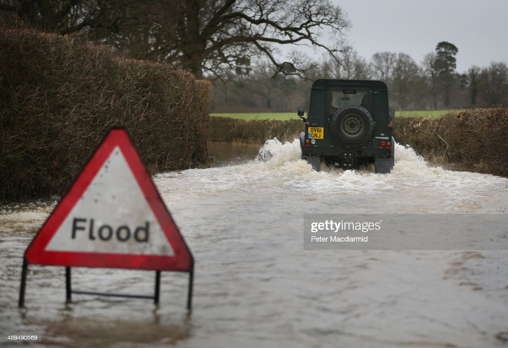 A Landrover makes it's way along a flooded road near Lingfield on December 27, 2013 in England. High winds and flooding are continuing to cause problems in parts of southern England. Some homes are still without power.