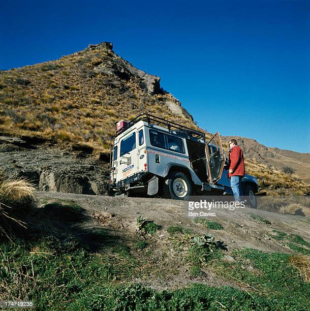 A landrover transports tourists along Skippers Road to admire the magnificent scenery of mountain peaks gorges and the fast flowing Shotover River on...