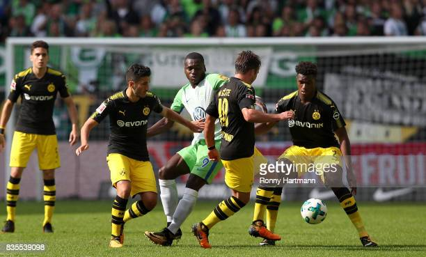 Landry Dimata of Wolfsburg competes with DanAxel Zagadou Mario Goetze Nuri Sahin and Marc Bartra of Dortmund during the Bundesliga match between VfL...
