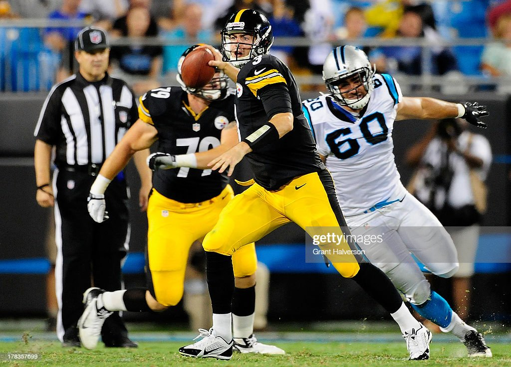 Landry Jones #3 of the Pittsburgh Steelers rolls out under pressure from Craig Roh #60 of the Carolina Panthers during a preseason NFL game at Bank of America Stadium on August 29, 2013 in Charlotte, North Carolina.