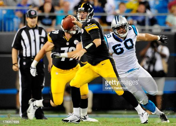 Landry Jones of the Pittsburgh Steelers rolls out under pressure from Craig Roh of the Carolina Panthers during a preseason NFL game at Bank of...