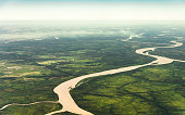 Landscape aerial view of colorful Amazon rivers, forest with trees, jungle, and fields