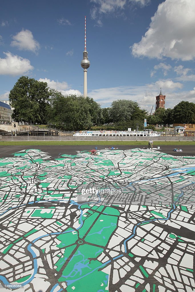 Landscape architect Lisa Hankow paints a giant map of Berlin in the city center the broadcast tower at Alexanderplatz and City Hall (R) on August 6, 2012 in Berlin, Germany. The map, which will measure 50 meters X 50 meters when finished, is in the scale of 1:775 and is an art installation meant to coincide with 775th anniversary of Berlin, which the city will celebrate in October.