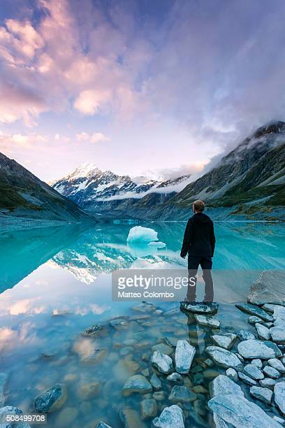 Landscape: hiker looking at Mt Cook from lake with iceberg, New Zealand