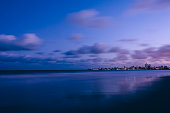 Landscape photo of an urban beach after sunset with purple sky and sea