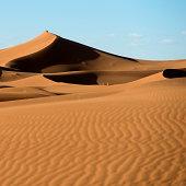 Landscape Of Drifted Sand Slopes Against A Blue Sky