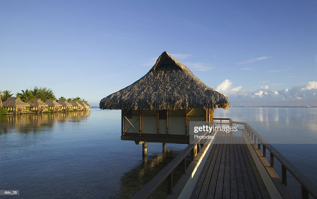 landscape photograph of a bridge and grass hut over a beautiful beach in the tropics : Stock Photo