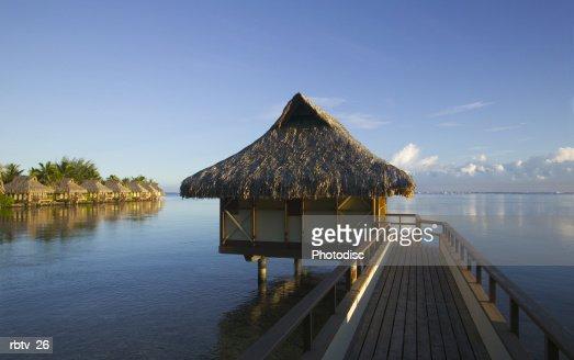 landscape photograph of a bridge and grass hut over a beautiful beach in the tropics : Foto de stock