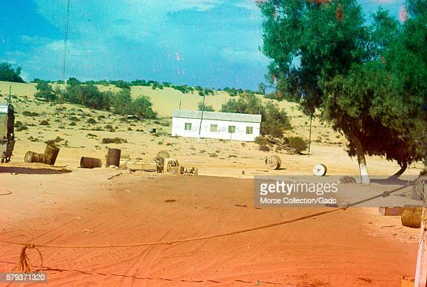 Landscape scene outside El Arish northern Sinai Gaza Israel of abandoned military equipment and a white barracks structure in the center midground...