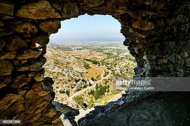 Landscape Seen Through Hole Of Stone Wall
