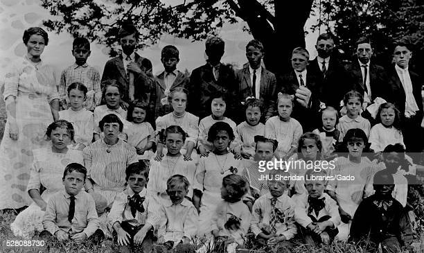 Landscape shot of schoolchildren all seated in grass under a tree one row standing all boys and girls wearing white school uniforms one African...