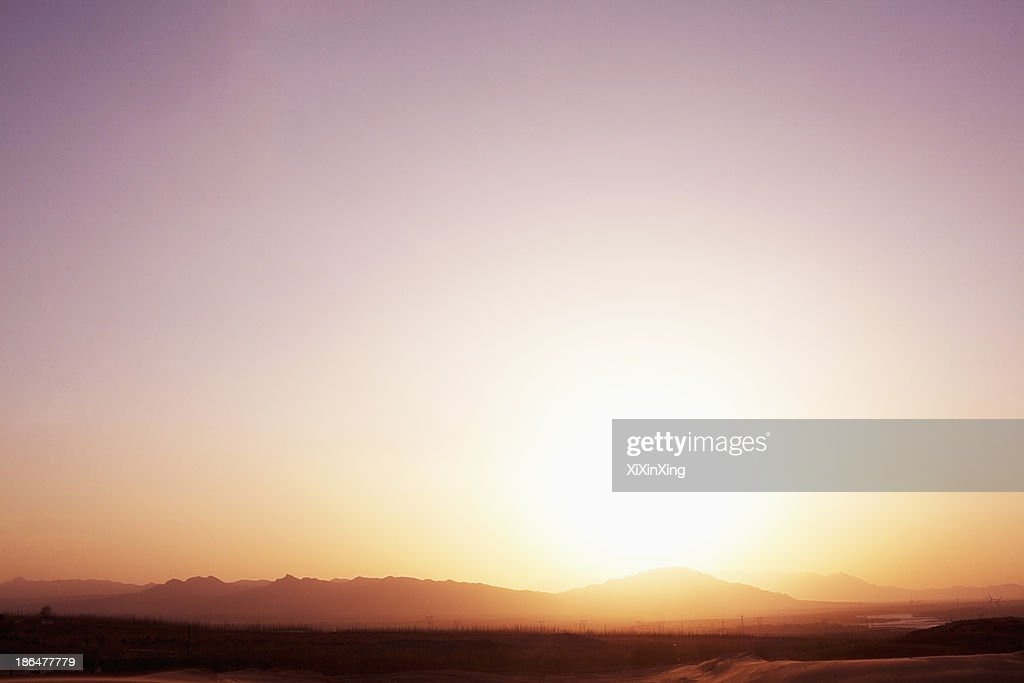 Landscape shot of sun coming down over the mountains in the desert, clear sky, China