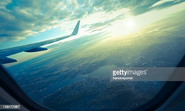 landscape view from airplane porthole on sunset