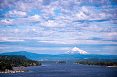 Panorama of Columbia River with forest banks and the marina, with a wavy blue water and the mountains on the horizon, which sticks out above the snow-covered Mount Hood, resting against a cloudy blue
