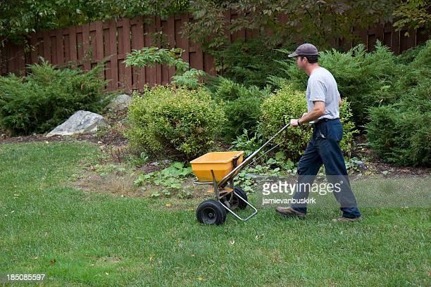 Landscaper Fertilizes a Lawn