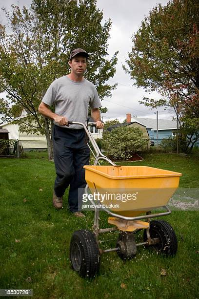 A landscaper pushing a fertilizer spreader around his lawn