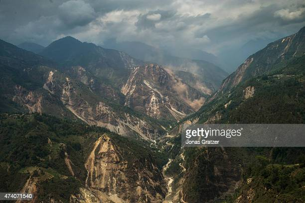 A landslide spreads a cloud of dust in to the air in one of the many deep valleys of the region on May 17 2015 in Nepal The devastating magnitude 78...