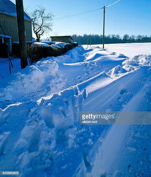 Landweg im Winter durch meterhohe Schneeverwehungen unpassierbar