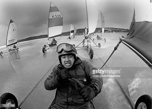 A landyachting or landsailing competitor grimacing and clutching the rope during a race along a beach circa 1980s