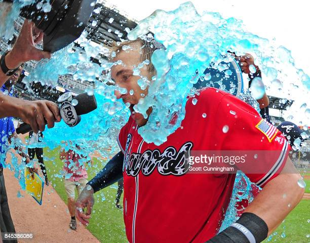 Lane Adams of the Atlanta Braves is doused by Micah Johnson after hitting a 10th inning tworun walkoff home run against the Miami Marlins at SunTrust...