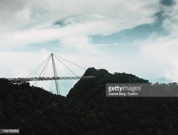 Langkawi Bridge Amidst Mountains Against Cloudy Sky