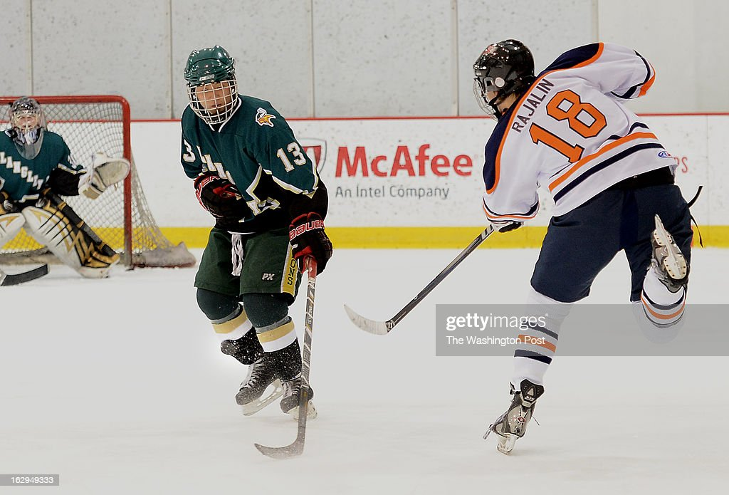Langley's Peter Nam, left, blocks the shot by Briar Woods Kim Rajalin, right, with his shin during the Northern Virginia Scholastic Hockey League Championship game held at the Kettler Capitals IcePlex on Friday, March 1, 2013. Briar Woods defeated Langley 7-2 for the title.