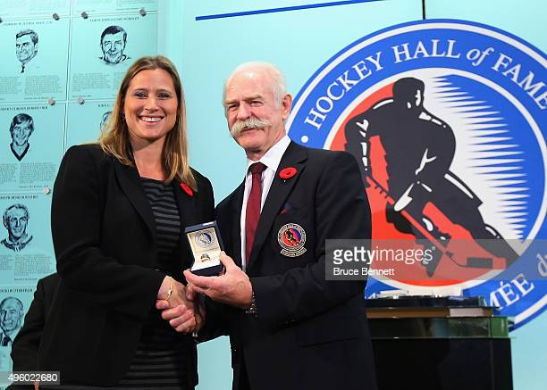 Lanny McDonald Chairman of the Hockey Hall of Fame presents Angela Ruggiero with her Hall of Fame ring at a photo op at the Hockey Hall of Fame and...