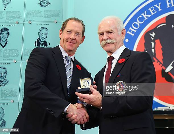 Lanny McDonald Chairman of the Hockey Hall of Fame presents Phil Housley with his Hall of Fame ring at a photo op at the Hockey Hall of Fame and...