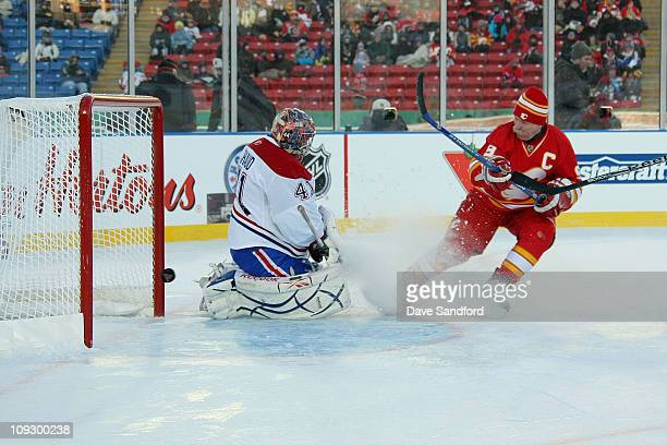 Lanny McDonald of the Calgary Flames Alumni team puts a shot on goal against goaltender Eric Fichaud of the Montreal Canadiens Alumni team during the...
