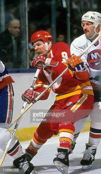 Lanny McDonald of the Calgary Flames fights for position with Ken Morrow of the New York Islanders circa 1988 at the Nassau Coliseum in Uniondale New...