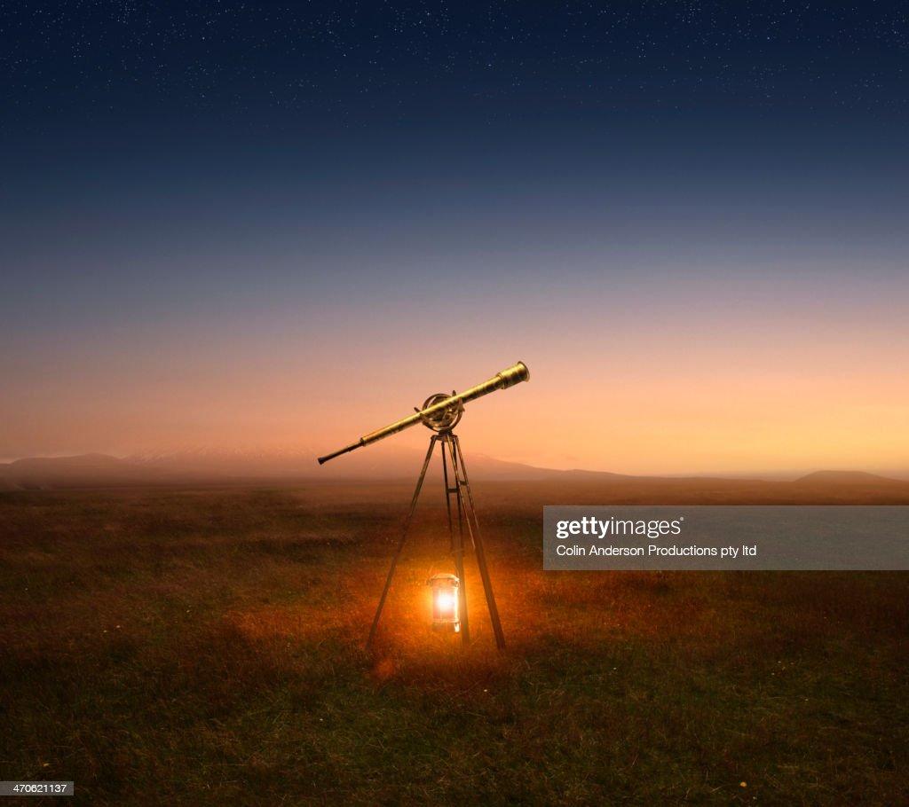 Lantern and telescope in rural field : Stock Photo