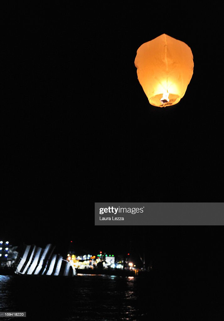 A lantern released by relatives of the victims of the sunken Costa Concordia flies into the sky after a minute of silence was held to mark the exact time the ship crashed, on January 13, 2013 in Giglio Porto, Italy. A year after the sinking of the ship Costa Concordia, relatives of the victims, survivors, island residents, law enforcement and institutions gathered to mark the first anniversary and commemorate the dead. More than four thousand people were on board when the ship hit a rock off the Tuscan coast, killing 32 and leaving two people missing.