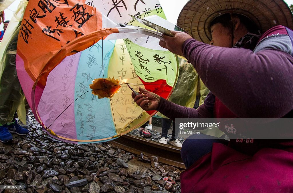 A lantern seller helps to launch a lantern at the Pingxi Sky Lantern Festival on February 14, 2016 in Pingxi District, New Taipei City, Taiwan. The event is the second of three organised lantern releases and the theme for the launch is 'Two Hearts Together'. Participants were encouraged to 'leave their love in Pingxi' and draw hearts on their lanterns.