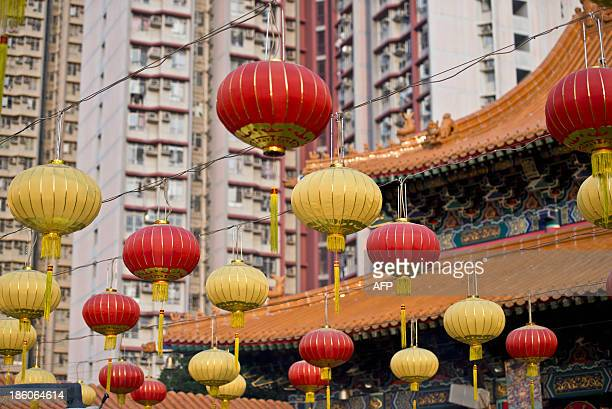 Lanterns at the Wong Tai Sin temple are seen in front of an apartment complex in Hong Kong on October 28 2013 The Taoist temple is a major tourist...